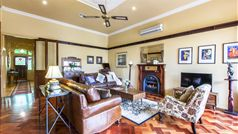 generous living room with gas log fire, leather sofas and parquetry floor