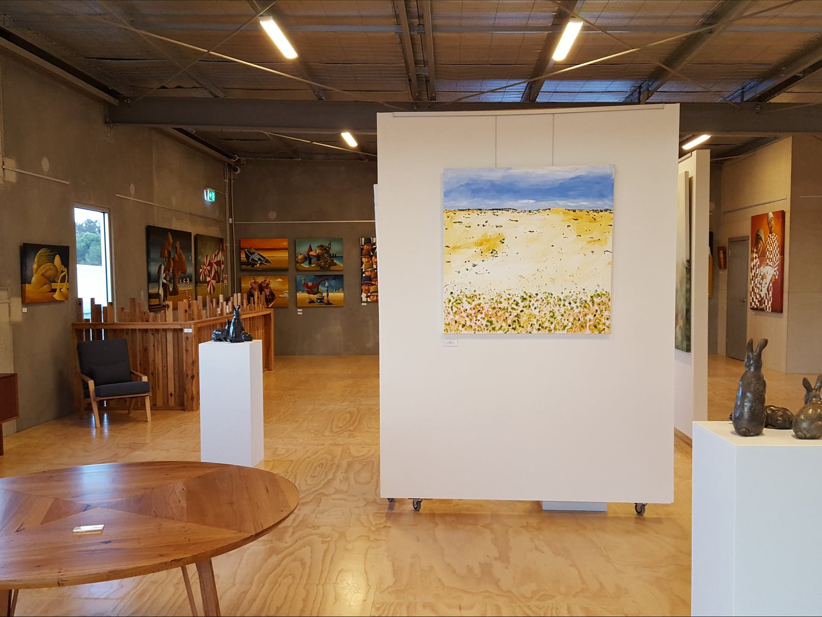 Various works on display upstairs at The Hive Gallery, showing sculpture, paintings and furniture.