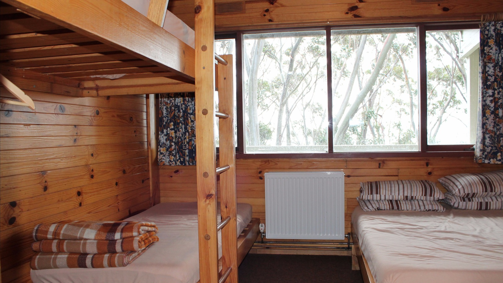 A room at Edski Lodge, a double bed with a set of single bunks with a view of snowgums out the windo