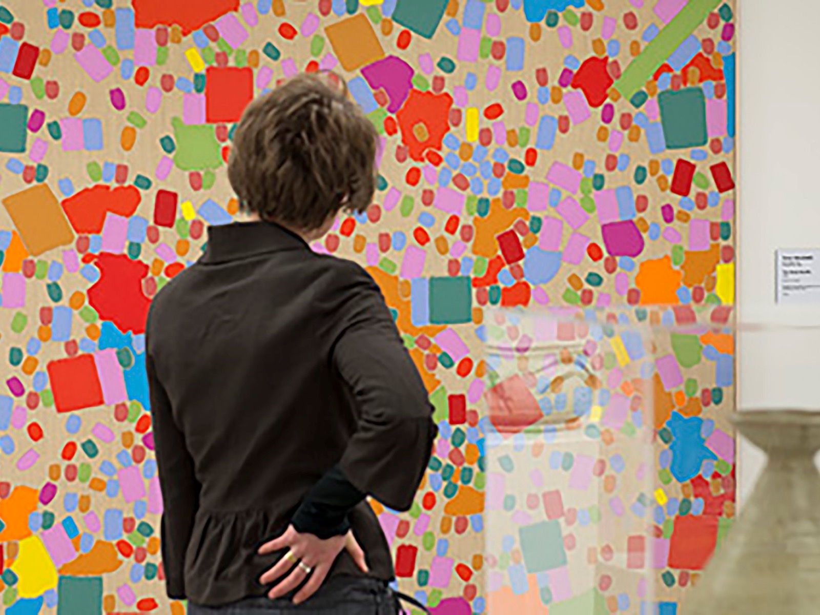 Visitor at Gippsland Art Gallery standing in front of a multicoloured artwork