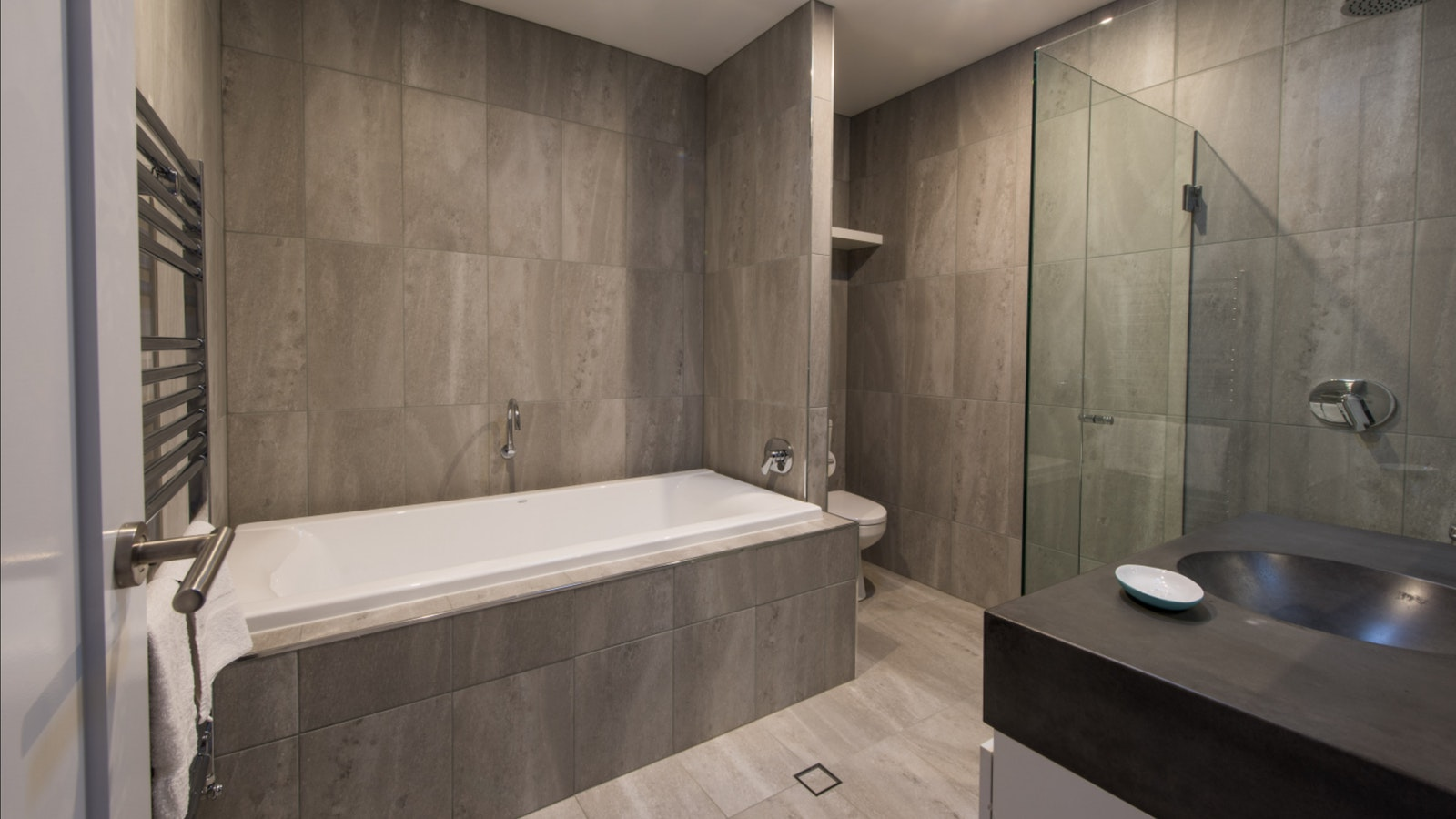 Main bathroom, grey tiled wet room with shower, deep bath, vanity and toilet.