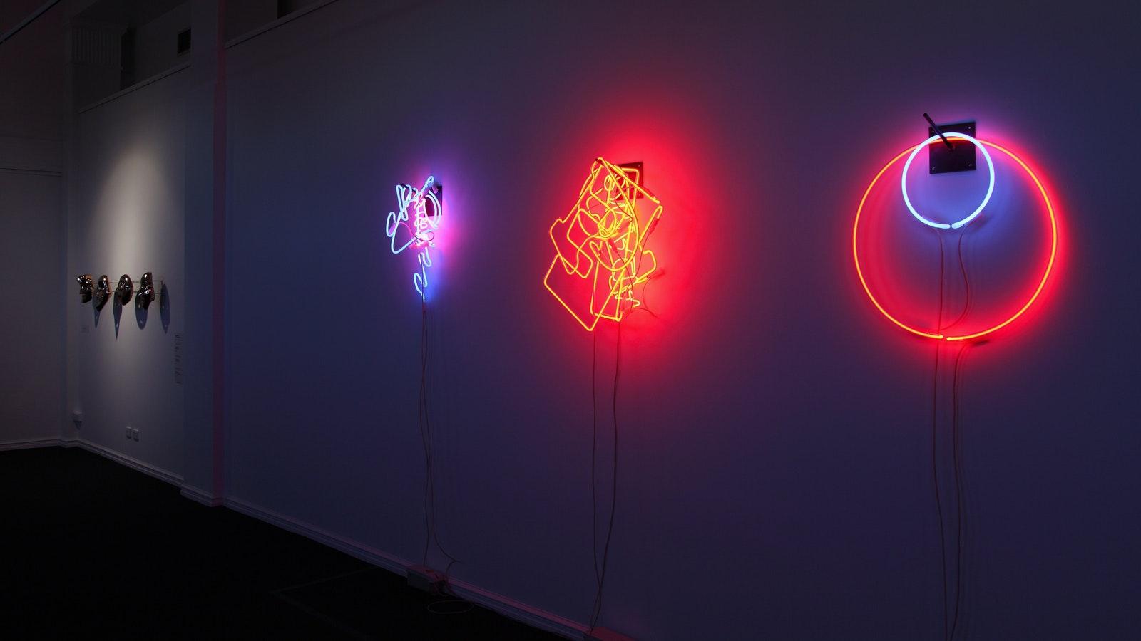 Bronze wall pieces by Darren Sylvester and neon works by Brendan Van Heck