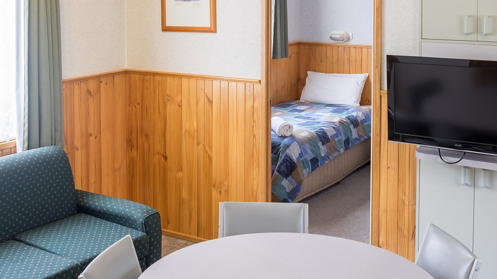 Family cabin with sofa, dining table and chairs, TV and access to bedroom.