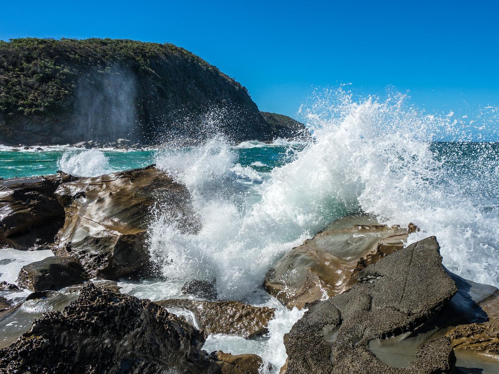 Sunny day at Blanket bay, waves crashing on rocks