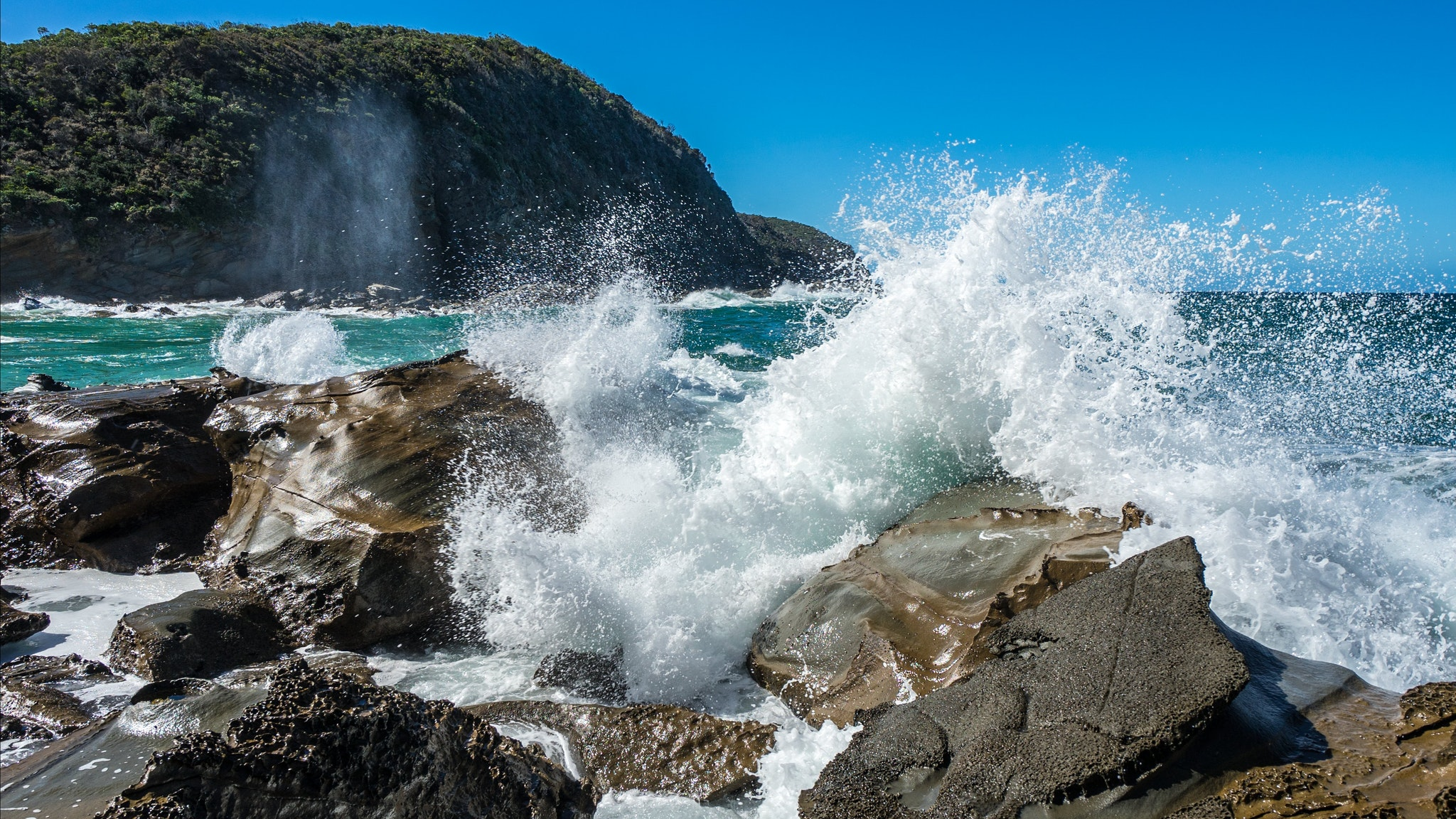 Sunny day at Blanket bay, waves crashing on rocks