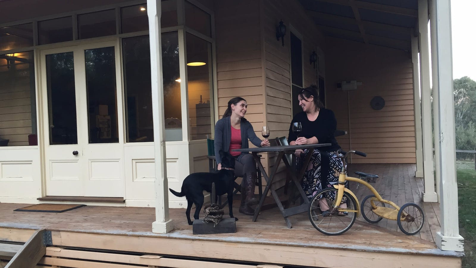 Ladies enjoying a wine on the Lottie's Cottage verandah with Mosey the dog