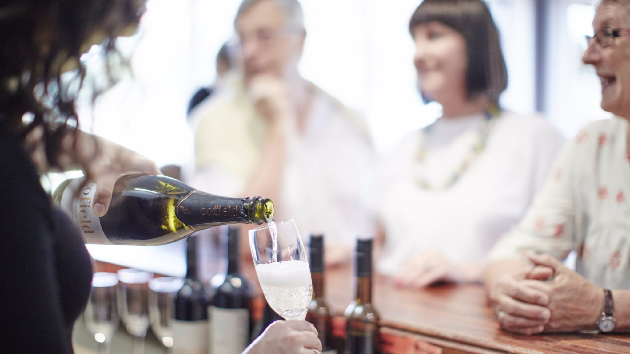 Staff serving Cofield Sparkling White wine to customers at Cellar Door