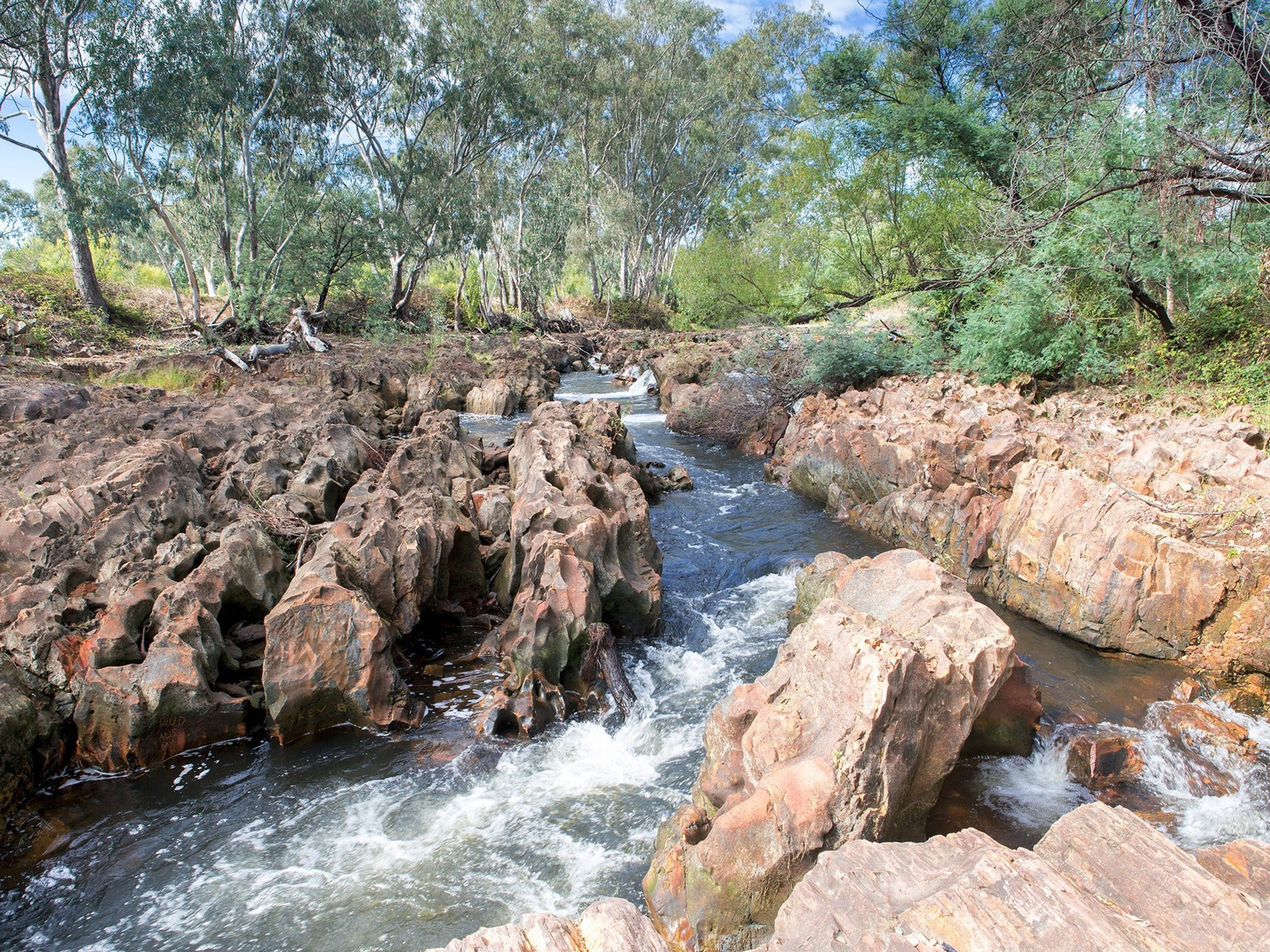 A small section of the river flowing through a section of red and orange water eroded rocks.
