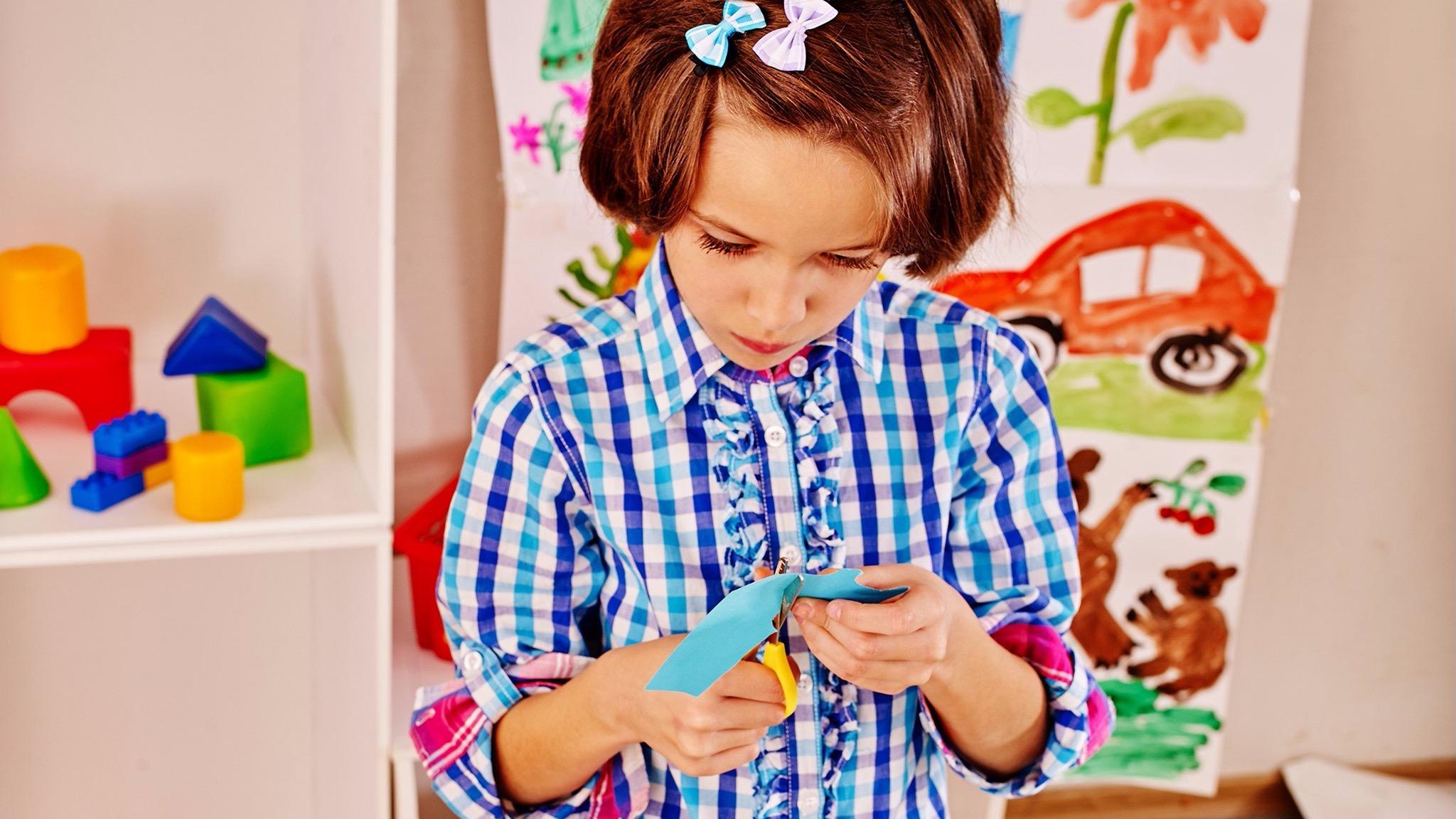Child cutting coloured paper