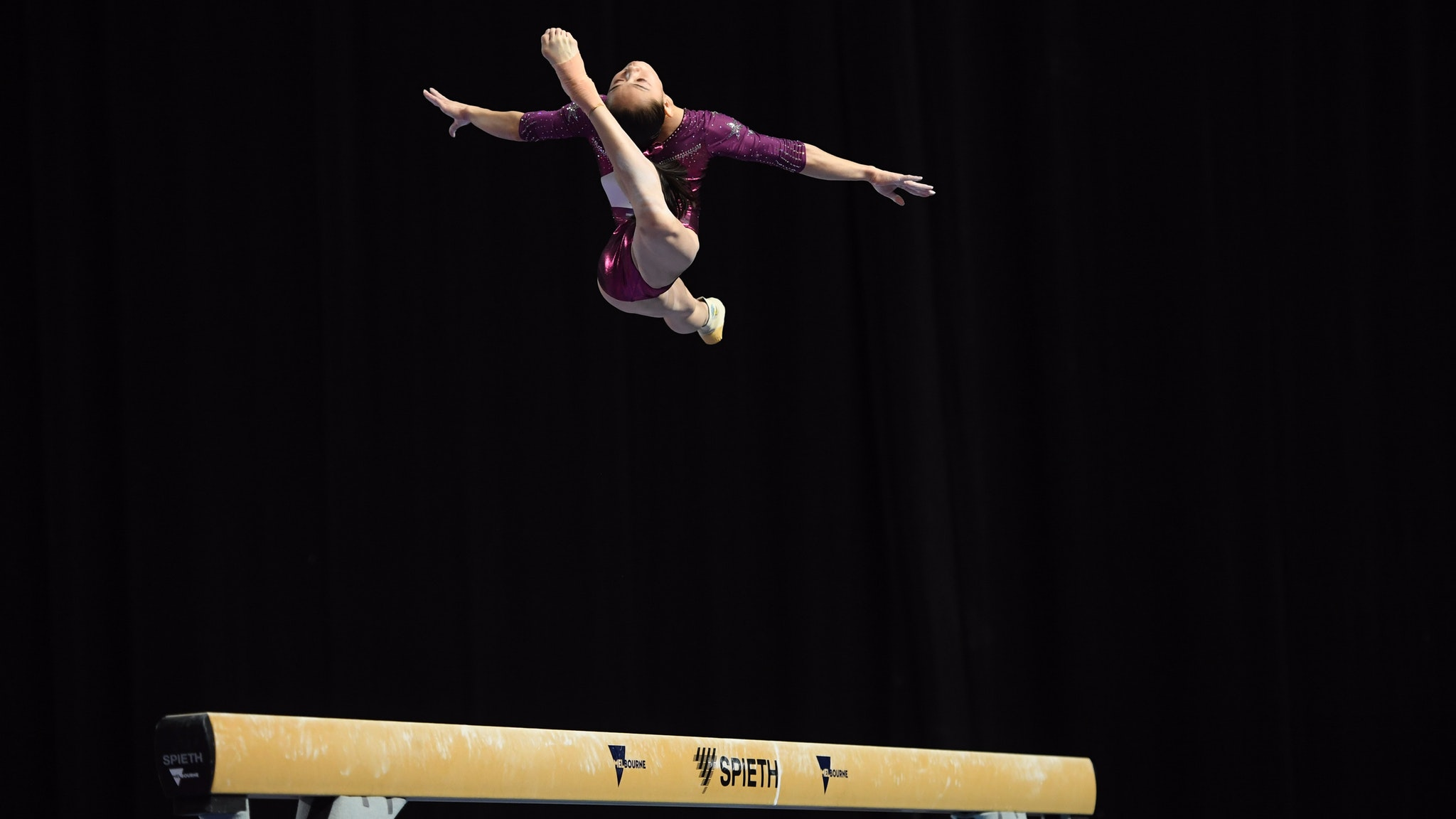 Female gymnast from China performing a ring leap on the Balance Beam