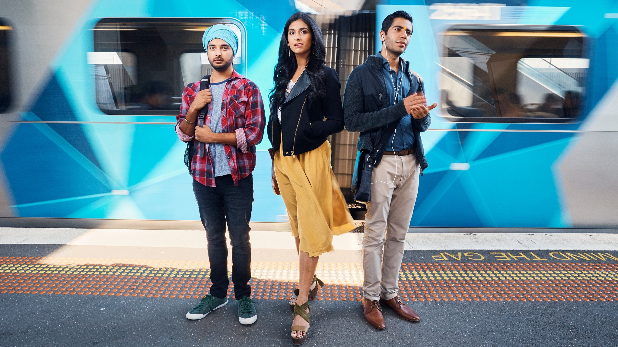 A young Indian woman and two young Indian men standing on a Melbourne train platform.