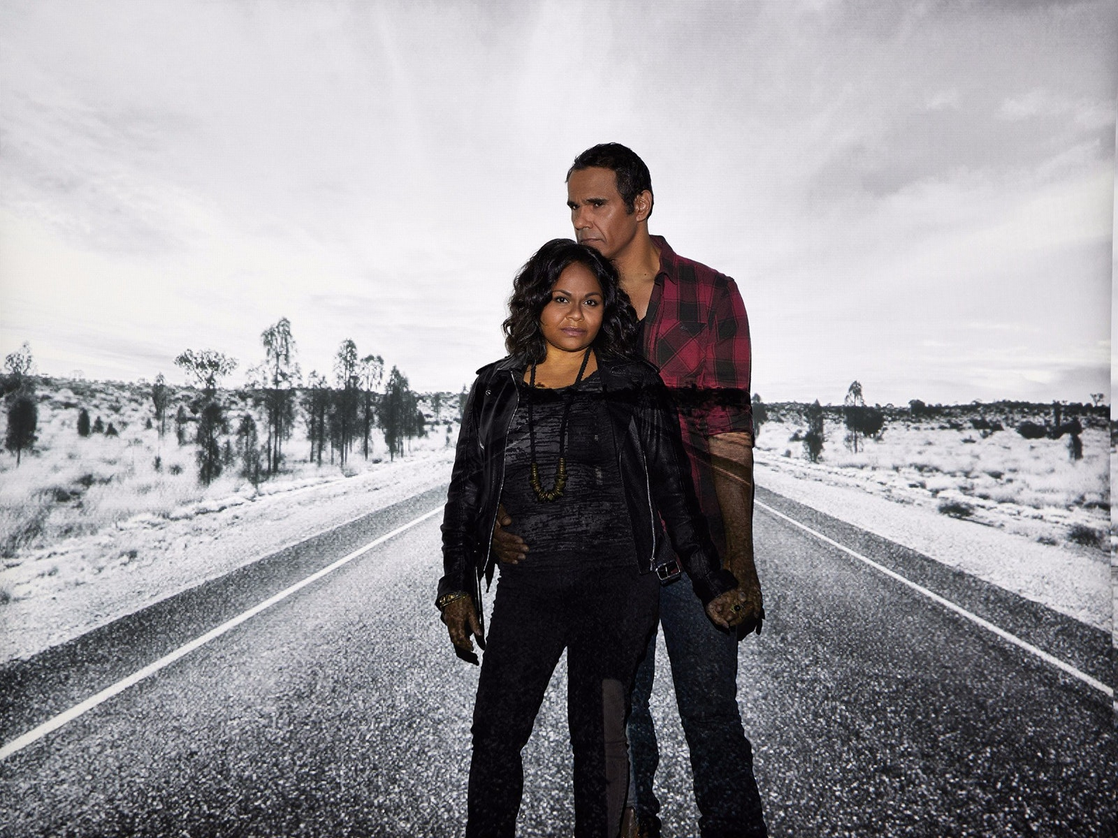 A man and a woman hold each other in front of a projection of an Australian country road.