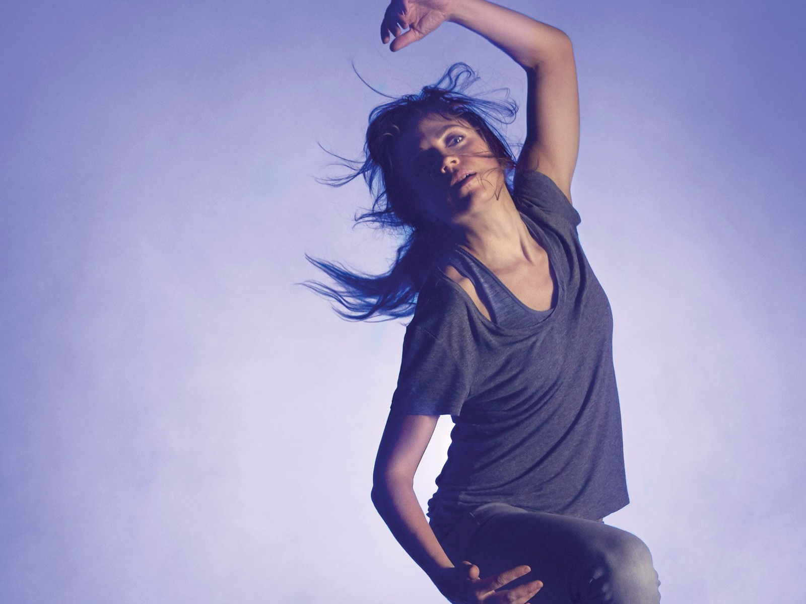 A woman dances, as if in a trance, across a background of blue light and smoke.