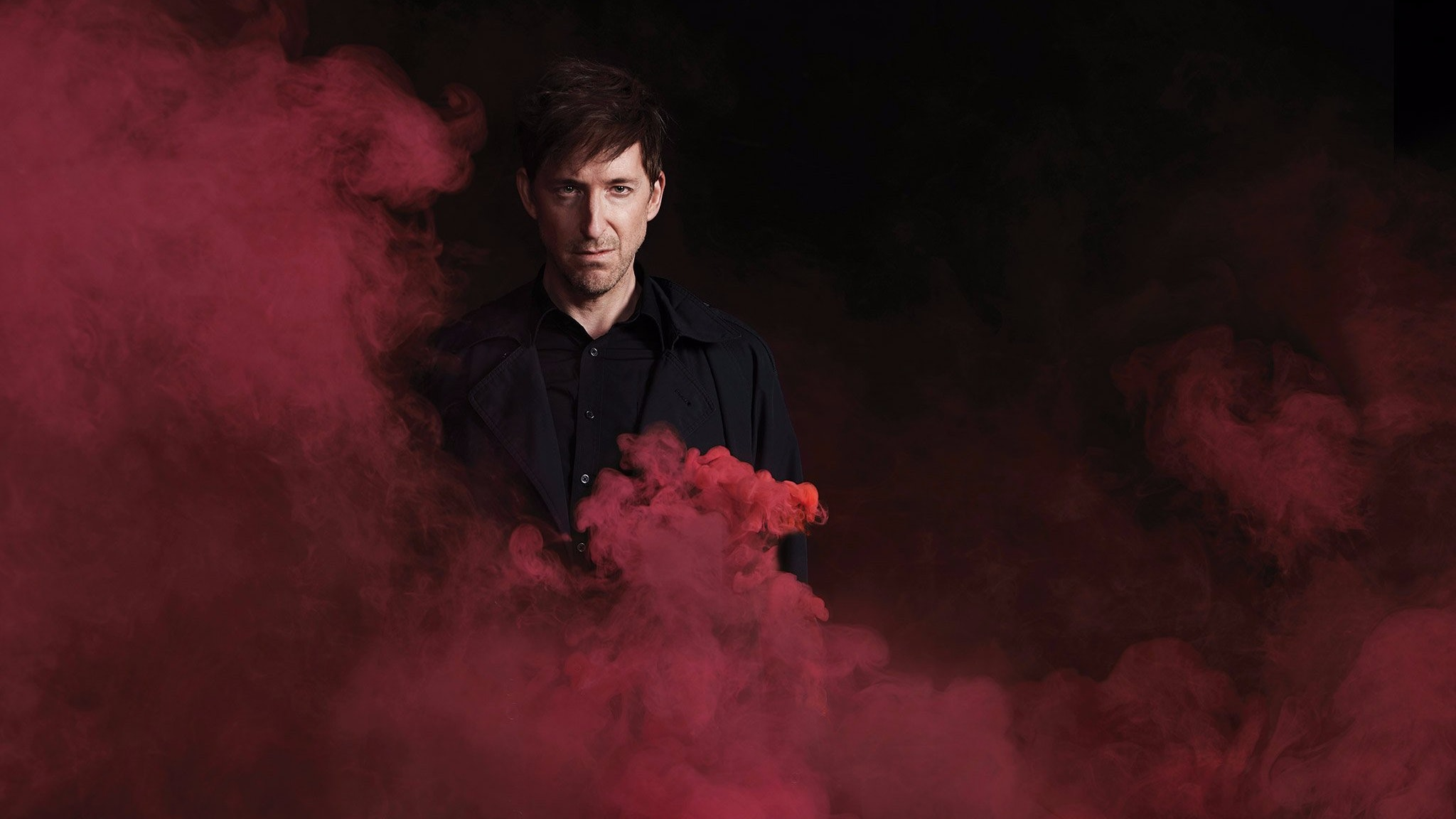 A man in black clothing looks directly forward as red smoke billows around him