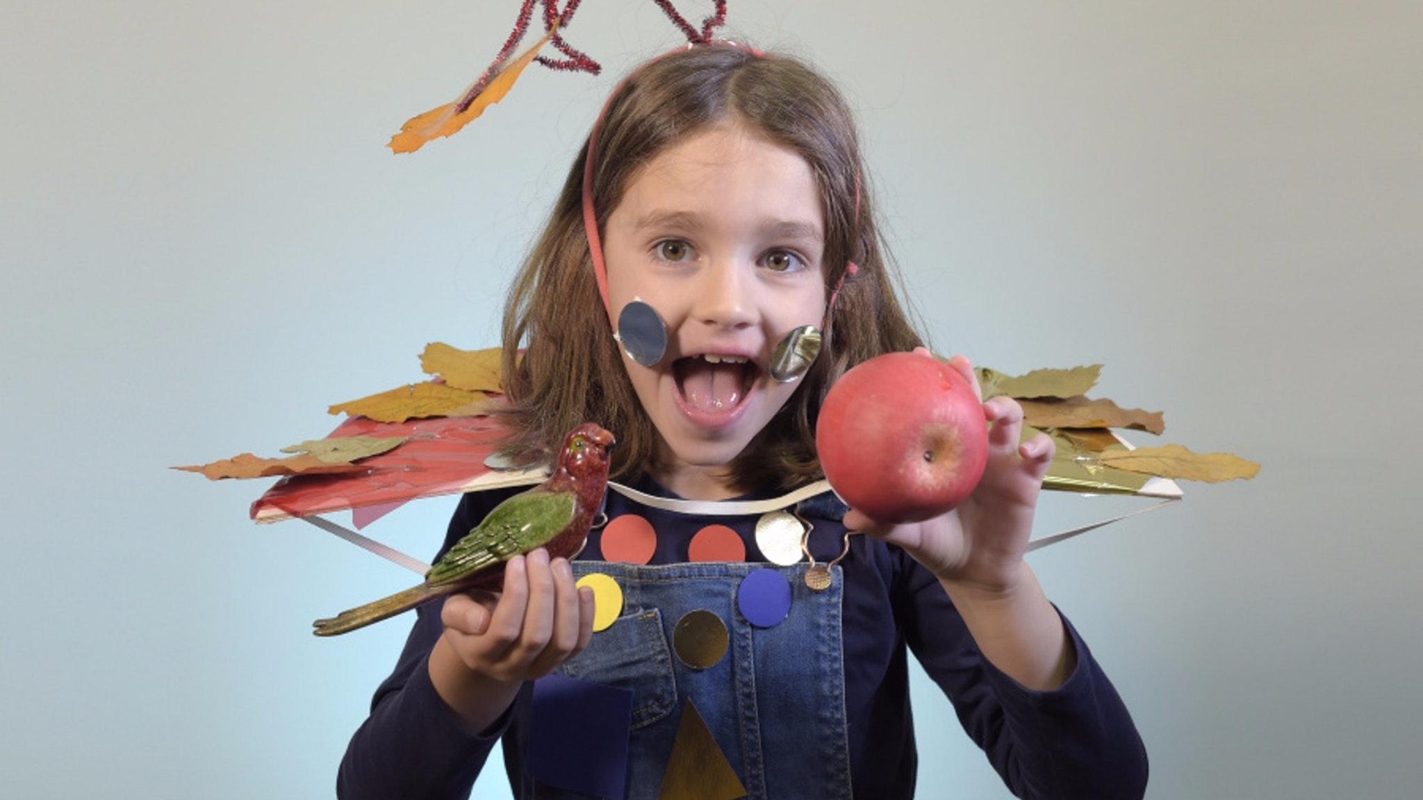 A little girl holding a porcelain bird and an apple on each hand