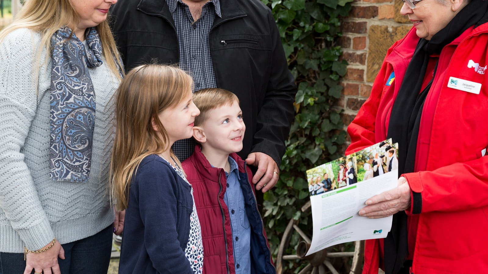 Family of four with focus on two children being shown a Cooks' Cottage fact sheet by volunteer