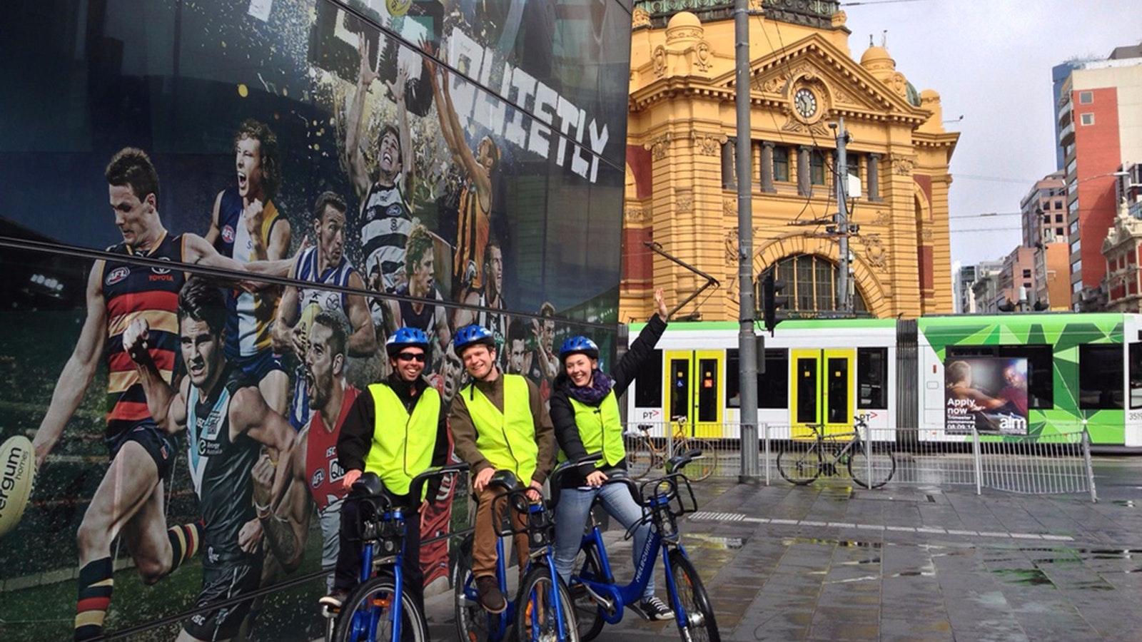 View of riders, tram and Flinders Street Station from Federation Square.