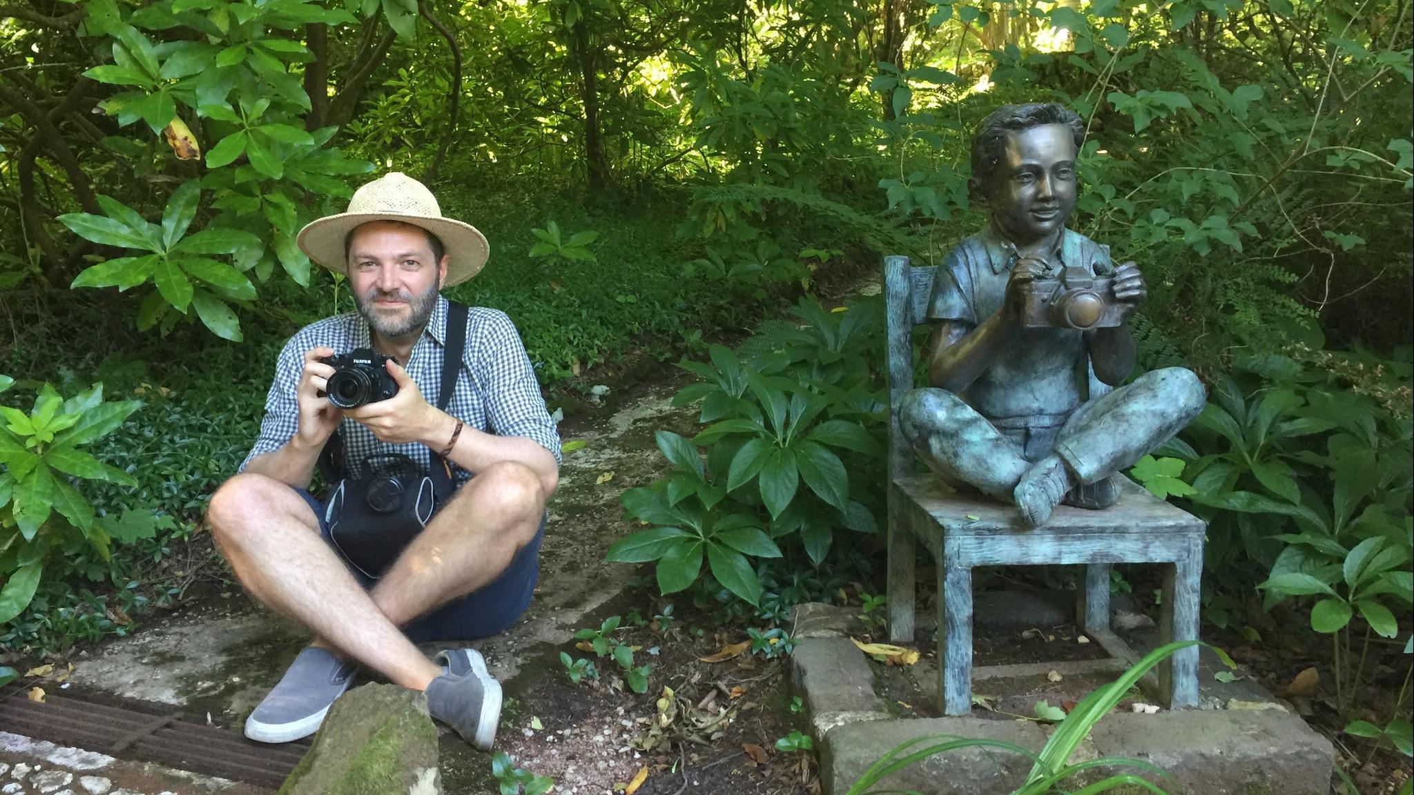 Life imitating art as Aaron poses alongside sculpture