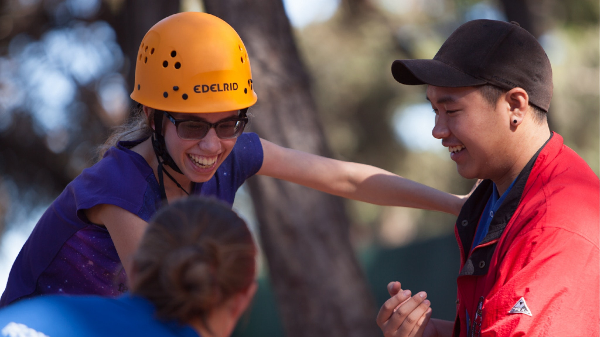 Image: Girl supported by volunteers on low ropes