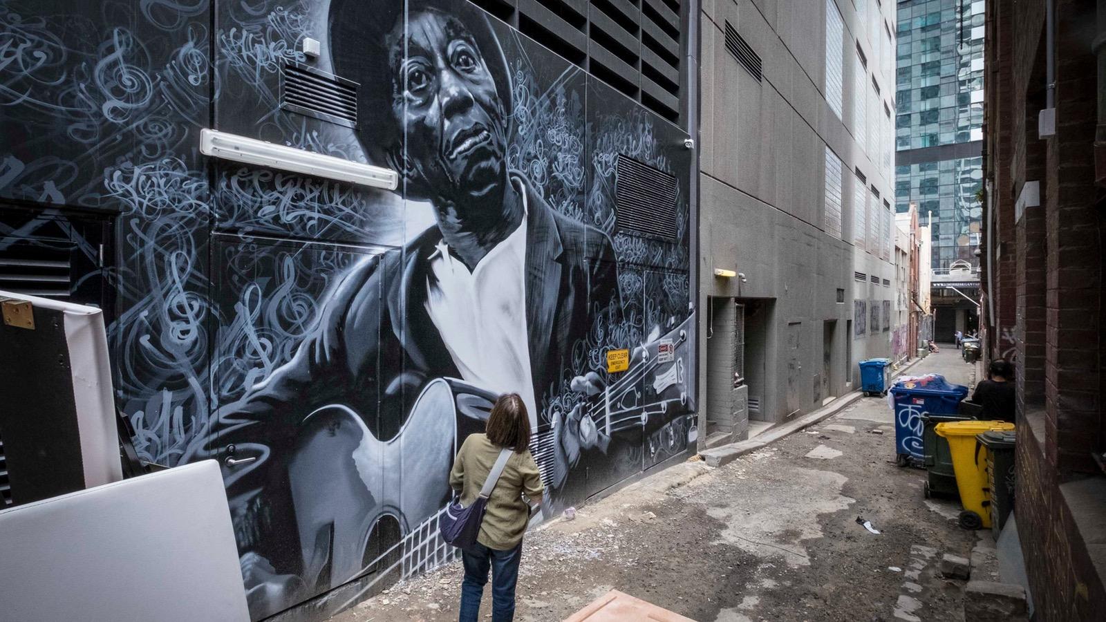 A woman looks at street art down a Melbourne laneway