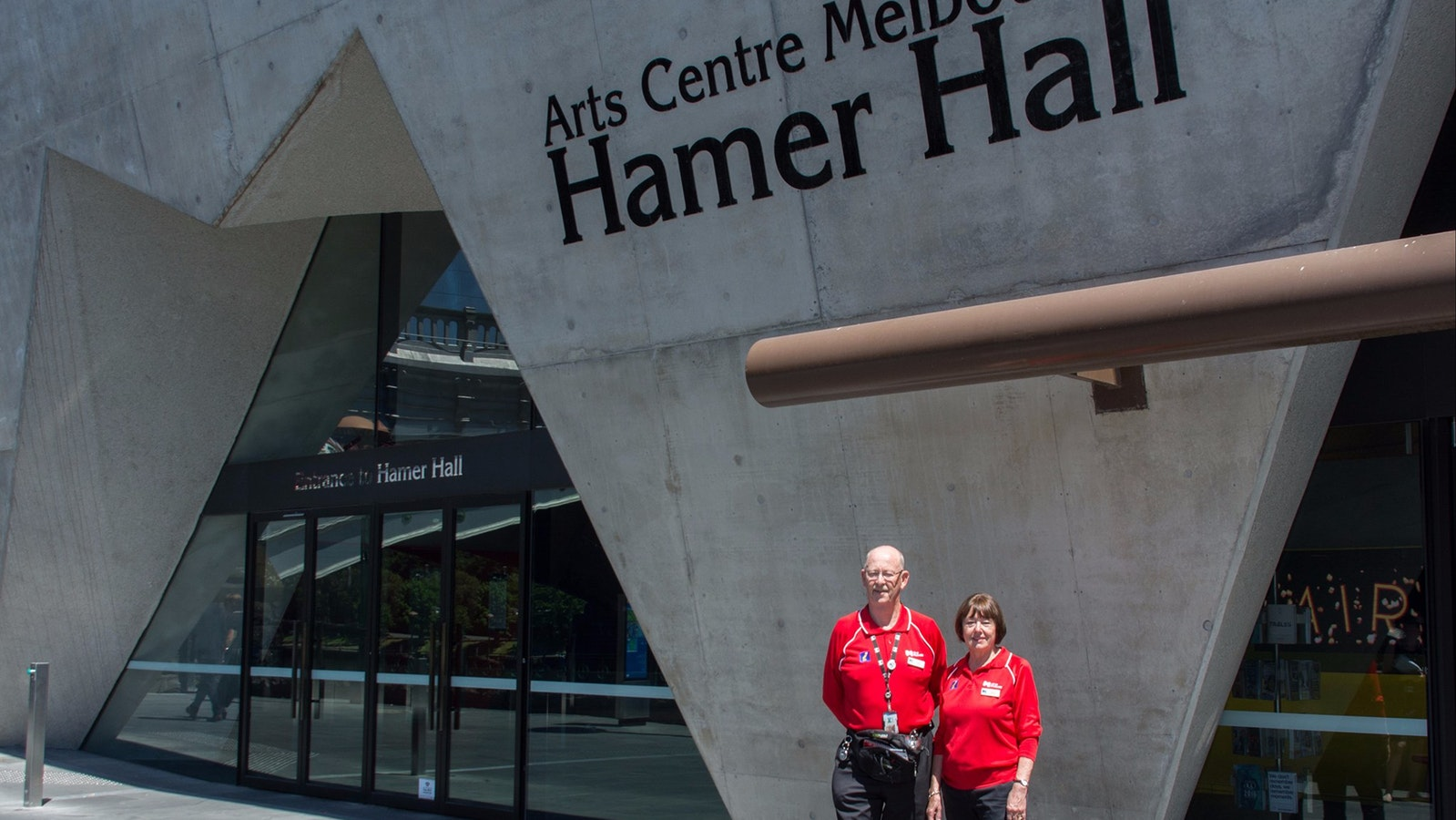 Two City of Melbourne volunteers wearing red shirts standing in front of entry to Hamer Hall