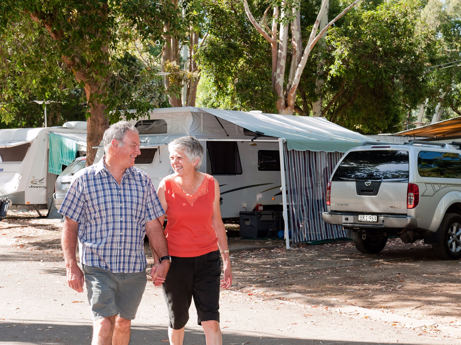 older couple holding hands and strolling through the holiday park