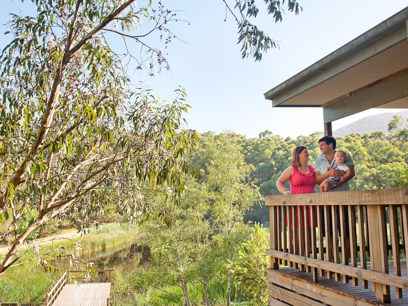 couple with child enjoying the view of lake piccaninny from the balcony of a hillside cabin