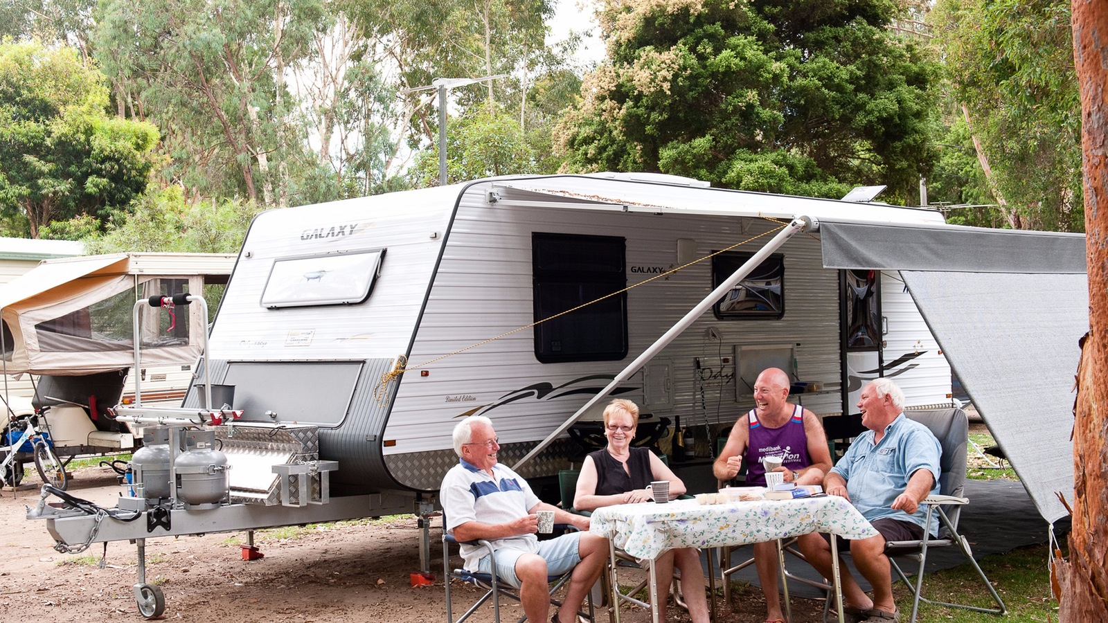 4 people enjoying a meal outside their caravan site at the holiday park