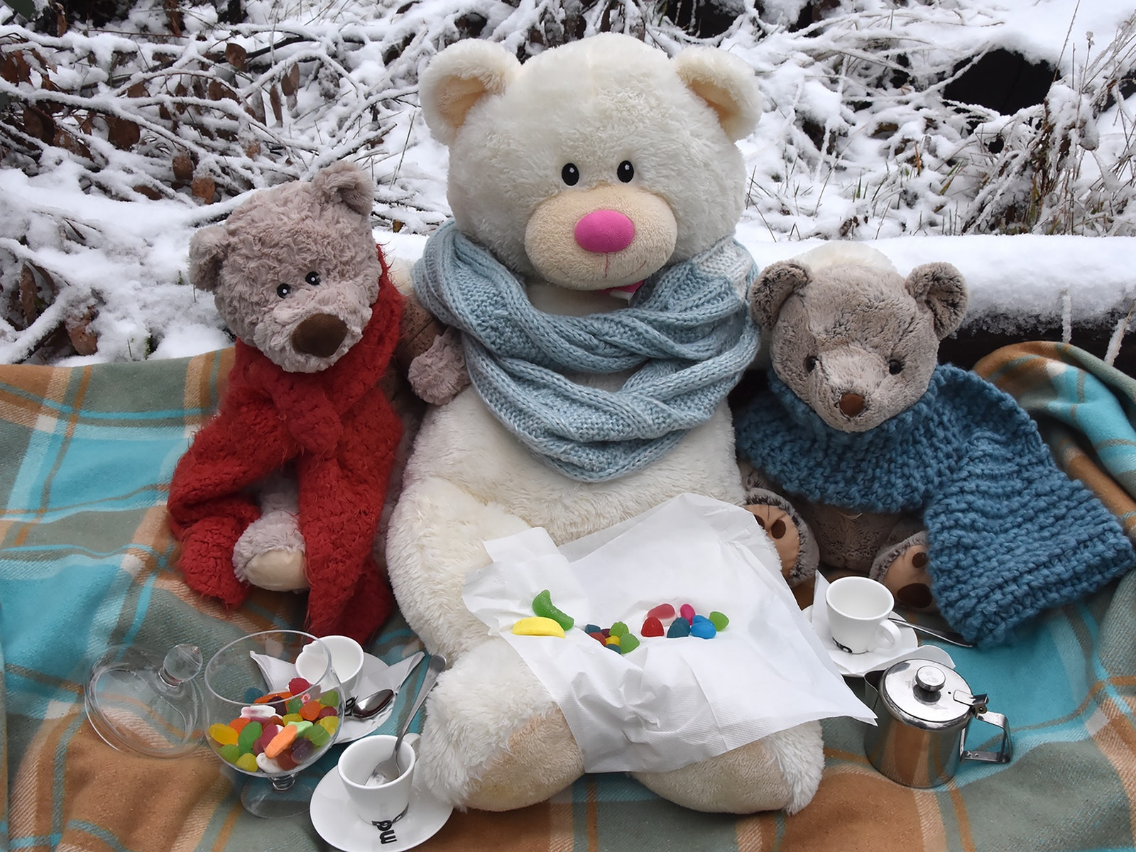 Three teddy bears enjoying a picnic on a rug in the snow