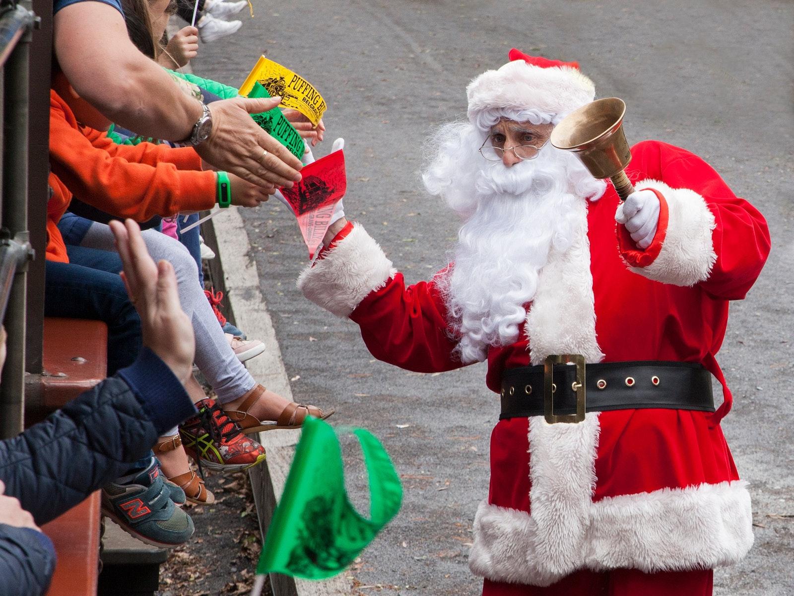 Santa hi-fiving children on Puffing Billy train