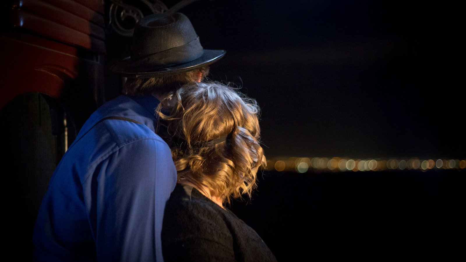 Couple watching Melbourne lights in the distance aboard Steam & Cuisine After Dark