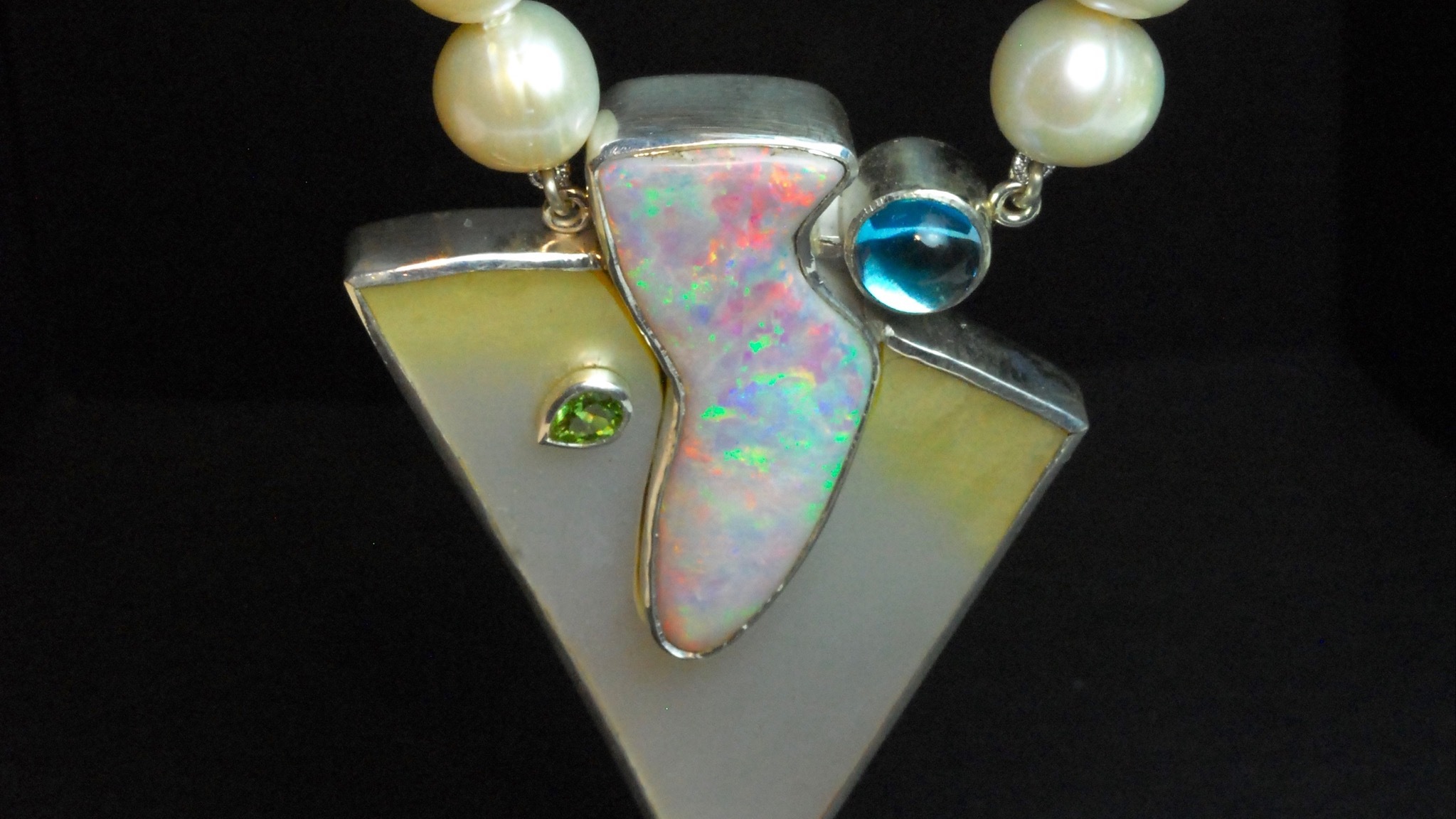 Opal, pearl shell, topaz and peridot pendant on pearls.