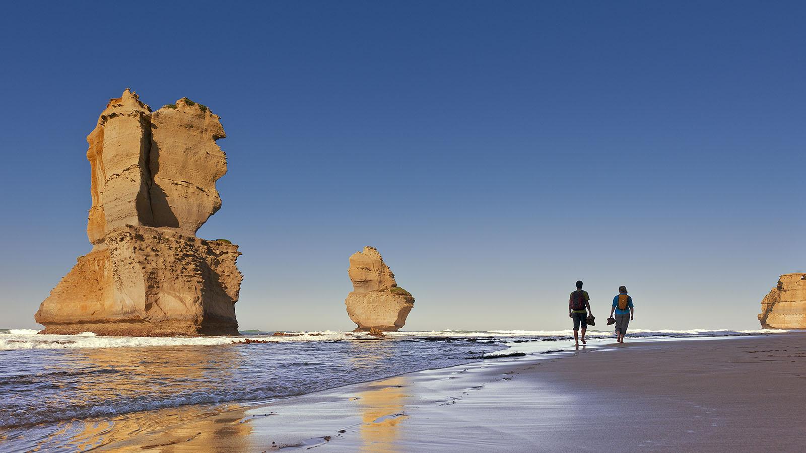 Couple walking past the 12 Apostles, Great Ocean Road, Victoria, Australia
