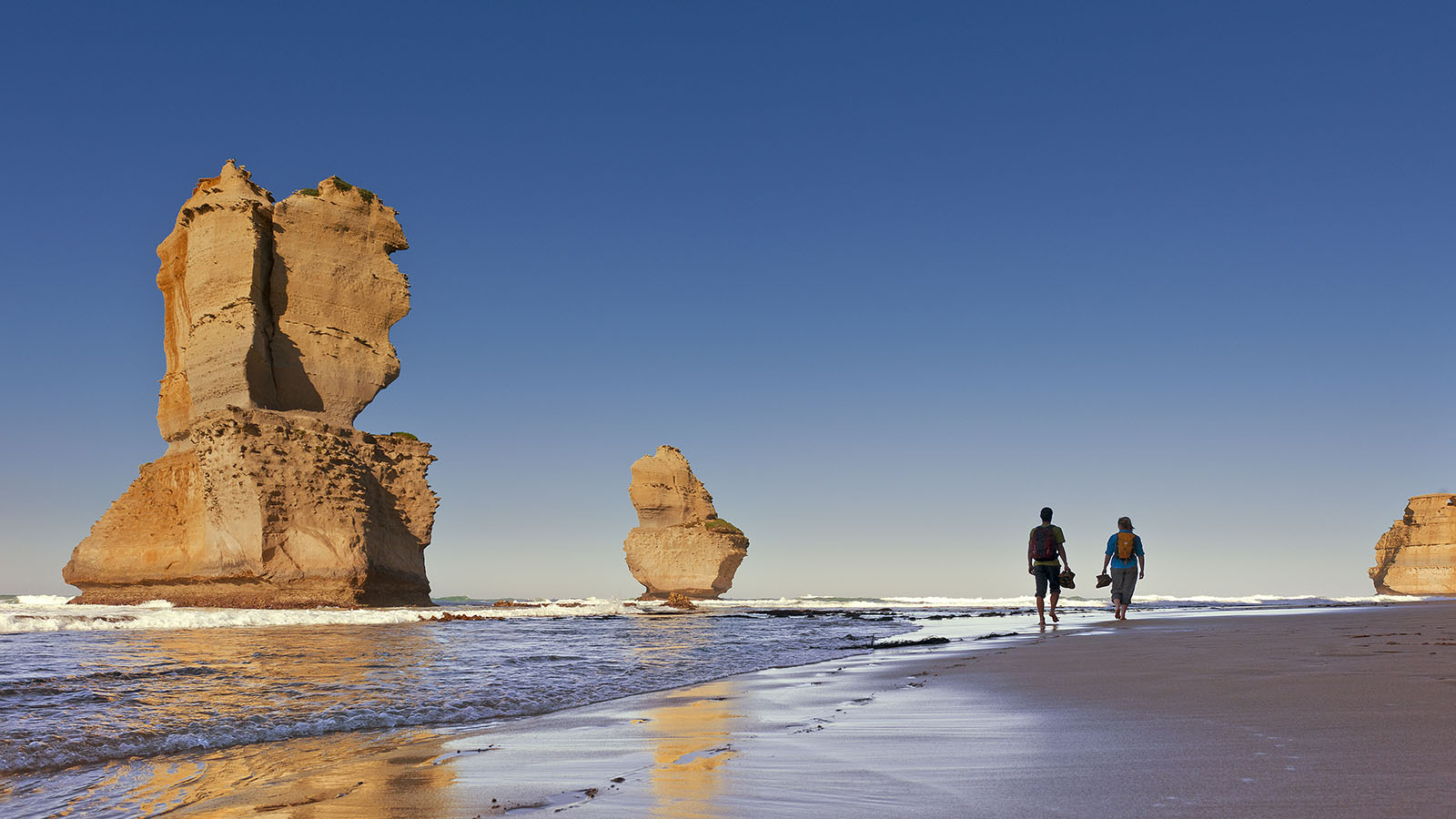 Couple walking past the 12 Apostles, Great Ocean Road, Victoria, Australia