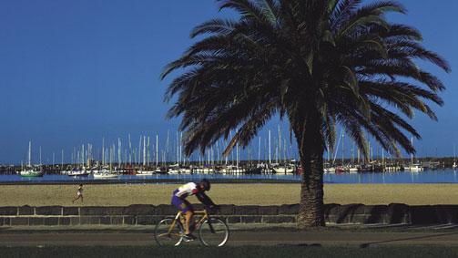 Cyclist rides along St Kilda foreshore, Melbourne, Victoria, Australia
