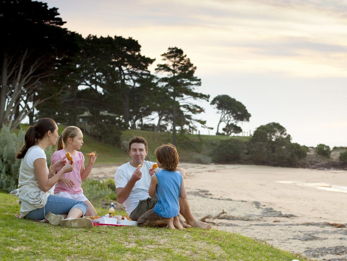 Family eating fish and chips on Cowes foreshore, Phillip Island, Victoria, Australia