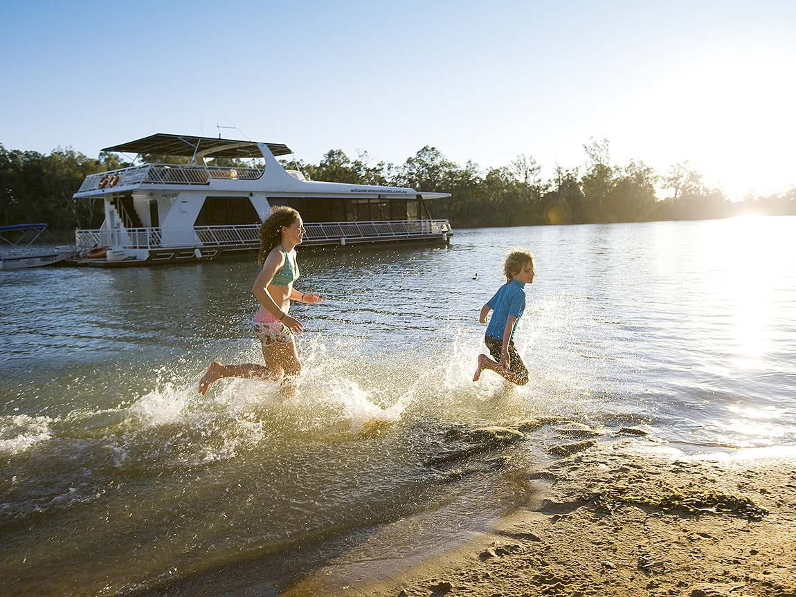 Kids play on the bank of the Murray River at Mildura, The Murray, Victoria, Australia