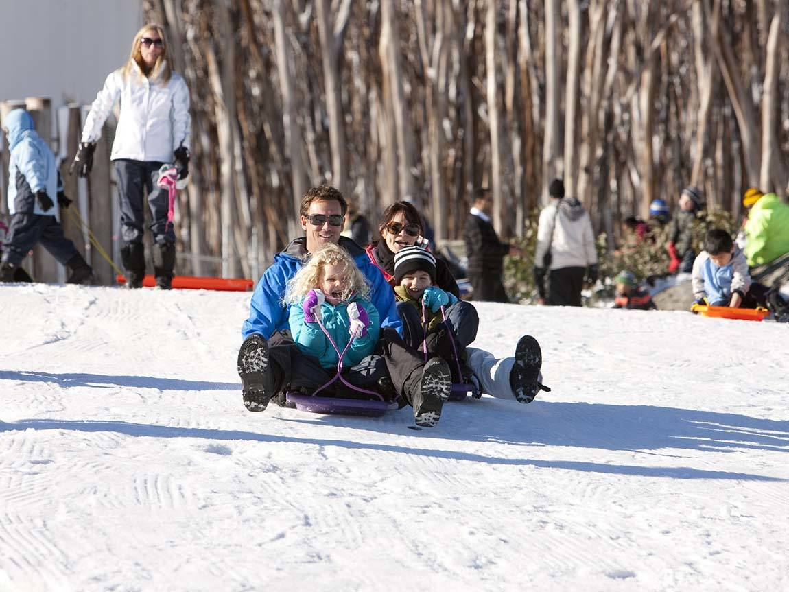 Family tobogganing down Lake Mountain, Yarra Valley and Dandenong, Ranges, Victoria, Australia
